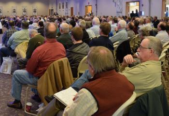 An estimated 600 men listen to a speaker at the conference.