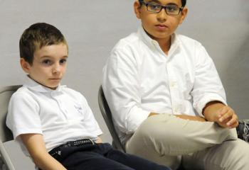 Sixth-graders Benjamin McCabe of St. Ann School, Emmaus, left, and Diego Mihura of St. Thomas More School, Allentown, await their turns.