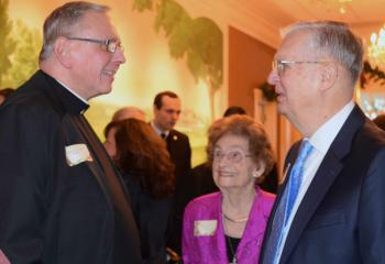 Msgr. Gerald Gobitas, left, speaks with William and Rose Scharle.