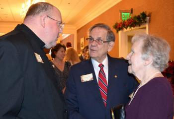 Msgr. David James, left, enjoys talking with Joseph and Elizabeth Bechtel.