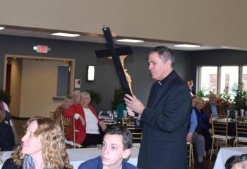 Father Philip Rodgers, pastor, carries a crucifix to be mounted in the parish hall.