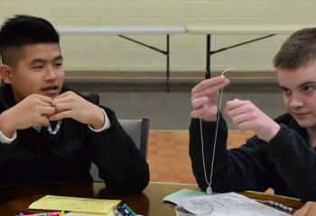 Andrew Nguyen, left, and Griffin Curtin assemble rosaries during the rally. (Photo by John Simitz)