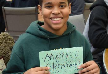 Julius Baker shows off a Christmas card he created for a prisoner. (Photo by John Simitz)