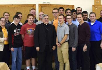 "Bishop of Allentown Alfred Schlert, center, welcomes young men and diocesan seminarians back after their camp experience at ""Do Whatever He Tells You."" Also reuniting with the young men are, Father Kevin Lonergan, right, assistant pastor of the Cathedral of St. Catharine of Siena, Allentown; Father Mark Searles, fifth from right, chaplain, Allentown Central Catholic High School; and Msgr. David James, fourth from left, diocesan vicar general and director of the Office of Vocations."