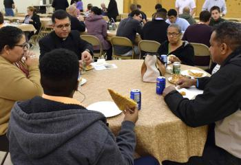 Father Angel Garcia Almodovar, center, pastor of St. Margaret, Reading, enjoys pizza with the family of a young man interested in learning more about vocations.