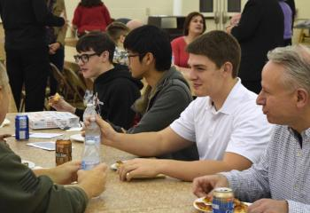 "John Maria, right, and Keaton Eidle, second from right, diocesan seminarians, talk with young men about their experience at ""Quo Vadis."""