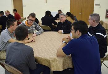 "Bishop of Allentown Alfred Schlert, center, listens to young men reflect on their experience at ""Quo Vadis."" Also seated at the table are, clockwise from right: Father Kevin Lonergan, seminarian Giuseppe Esposito, Keith Neidig, Ben Scheaffer and Gerard Behe."