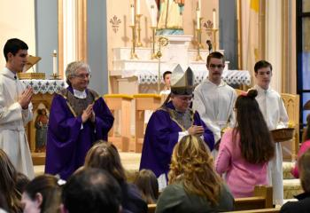 Emily Yuschock presents the offertory gifts to Bishop Alfred Schlert. (Photo by John Simitz)