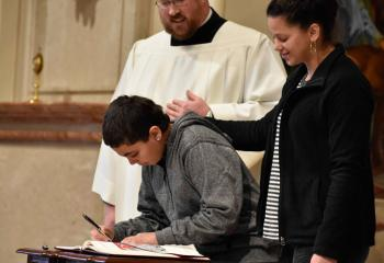 Jimmy Torres signs the Book of the Elect with the support of Anais Vega, right, and Father Allen Hoffa, administrator of St. Joseph, Summit Hill.
