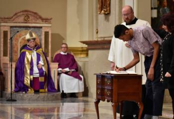 Bishop Schlert, left, witnesses a catechumen with his godmother sign the Book of the Elect.