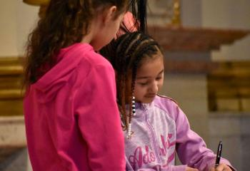 Crystal Delgado signs the Book of the Elect with encouragement from her sister, Sadie Delgado.