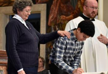 "Joseuien Aceuedo becomes ""elect"" after signing the Book of the Elect under guidance from Sister Margaret Pavluchuck, director of religious education at St. Peter the Apostle, Reading."