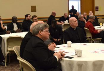 Bishop Alfred Schlert, left, and priests listen to Bishop William Waltersheid's morning presentation.