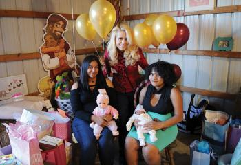 Surrounded by gifts, Maggie Sweet stands with Nashaly Cruz Pagon, seated left, and Shannet Cuascut holding her 6-day-old son Jaivian Rosario Oct. 22 at a baby shower for the two young women that was organized by pro-life members of Forty Days for Life and Silent No More from the Lehigh Valley and Norristown. (Photo by Ed Koskey)
