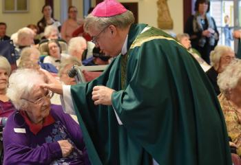 Bishop Schlert anoints Ruth Neff with blessed oil while performing the Sacrament of the Anointing of the Sick.