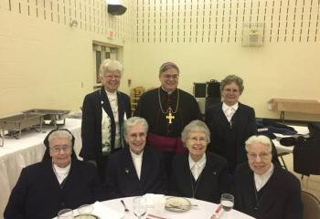 Bishop Alfred Schlert with members of the Sisters, Servants of the Immaculate Heart of Mary at the dinner, from left: front, Sister Miriam Dennis Sculley, Sister Teresa Paul, Sister Marian Bernadette Chuk and Sister Marie Eugene Reed; back, Sister Anita Gallagher, Bishop Schlert and Sister Lorraine Holzman.