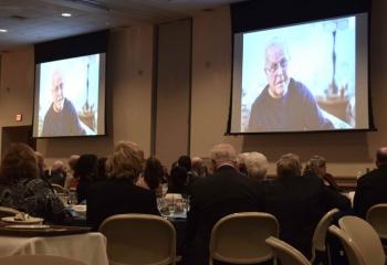 Charles Klinesmith is on the screen during the Catholic Charities video.
