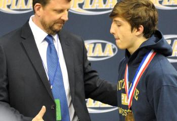 NDHS head wrestling coach John McGuire, left, congratulates his son, Ryan, before the 132-pound weight class medal ceremony at the PIAA Class AA mat tournament. McGuire finished fifth in the state.