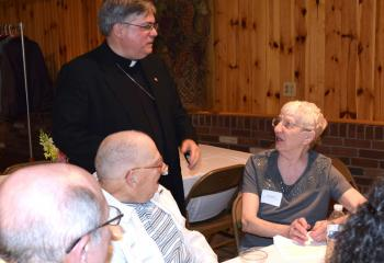 Bishop Alfred Schlert, left, converses with George and Jean Bruker, parishioners of Immaculate Conception, Jim Thorpe.