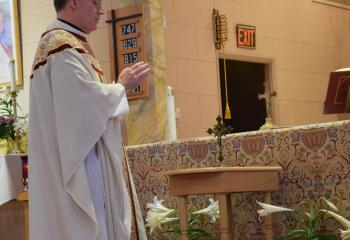 Father Robert Finlan, pastor of St. Joseph, Frackville, blesses the Traveling Vocations Crucifix to be hosted by a different parish family each month to increase prayers for vocations to the priesthood and religious life.