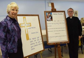 Sister Patricia Weidman, left, chaplain at the Federal Correctional Institution Schuylkill, and Father Finlan, pastor, stands alongside posters signed by parishioners.