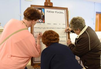 Parishioners sign a poster in tribute to Father Finlan and his call to the religious life.