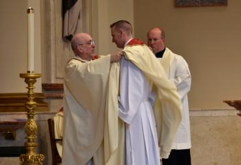 Monsignor Joseph DeSantis, left, vests Father Hutta during Investiture with Stole and Chasuble.