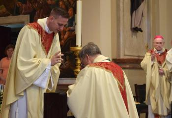 Father Hutta, left, bestows his first priestly blessing on Bishop Schlert.