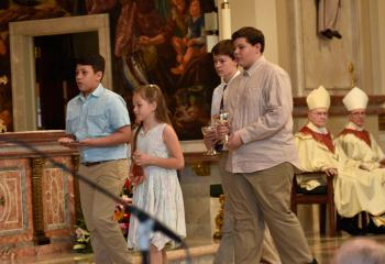 Father Hutta's niece and nephews present the offertory gifts during the Mass. From left are John Jacob Klein, Andi Jean Girard, and Jacob and Joshua Shelton.