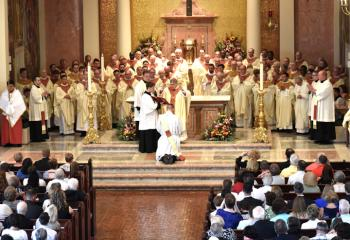 Bishop Schlert, priests of the Diocese of Allentown and visiting clergy pray over the newly ordained Father Hutta.
