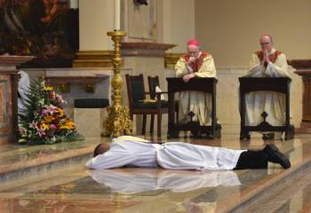 Then Deacon Hutta prostrates himself before the altar as Bishop Emeritus Edward Cullen, left, and Bishop Timothy Senior pray the Litany of Supplication.