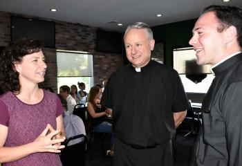 Kelly Anderson, left, chats with Deacon John Maria and seminarian Philip Mass during a break in the evening session.