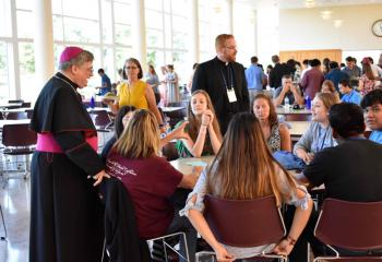 Bishop Alfred Schlert chats with families at a barbecue dinner cookout in DeSales University Center after the July 15 afternoon liturgy.