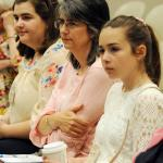 Magdalene Stratton, 16, left, her mother Deanna Stratton and sister Molly Stratton, 14, of Reading listen to Sister Faustina Maria Pia speak at the event.