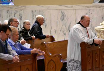 Gus and Shirley Heidecker, front left, join other Serrans praying as Monsignor David James leads the Rosary for Vocations.