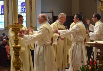 Deacons welcome the newly ordained at the Kiss of Peace.