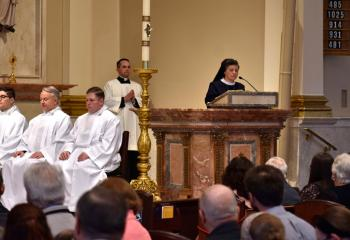 Sister Mary Jo Ely of the Sisters, Servants of the Immaculate Heart of Mary proclaims the first reading as lector. Listening are, from left, Deacon Giuseppe Esposito, Deacon John Maria, Deacon Zachary Wehr and Father Keith Mathur, director of the Diocesan Office for Divine Worship.