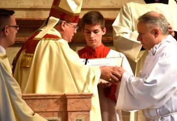 Candidate John Maria places his hands in Bishop Alfred Schlert's hands as he makes his promise of obedience. At far left is Deacon John Hutta.