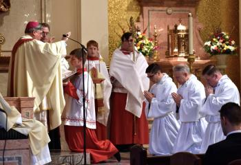 Bishop Alfred Schlert extends his hands over the deacon candidates, from left, Giuseppe Esposito, John Maria and Zachary Wehr during the Prayer of Consecration, the form of the Sacrament of Holy Orders. At the completion of this prayer, the three men are ordained deacons. At left is Monsignor Victor Finelli.
