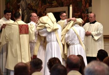 The newly ordained deacons are vested in the stole and dalmatic, which are the proper vestments for a deacon when assisting at Mass. Standing are, from left: Deacon Giuseppe Esposito, vested by Deacon Noe Ramirez de Paz; Deacon John Maria, vested by Deacon Rick Lanciano; and Deacon Zachary Wehr, vested by Deacon John Hutta. At right is Father Allen Hoffa.
