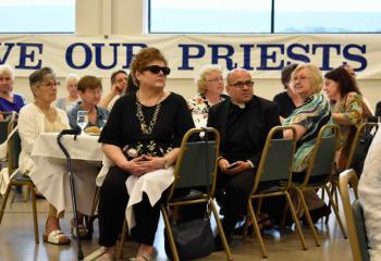 Father Robert George, pastor of Sacred Heart, Bethlehem, joins other guests in listening to Bishop Alfred Schlert's remarks. (Photo by John Simitz)