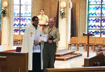 Father Eric Tolentino, left, presents the Rev. Joseph Campbell Award to Fred Flemming. Randy Bjorken watches from the lectern.