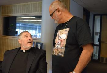 Monsignor John Campbell, left, pastor emeritus of Queenship of Mary, enjoys a conversation with Hector Lopez.