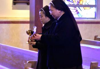 Sisters Apostles of the Descent of the Holy Spirit Sister Mary Jerome Kim and Sister Mary Francesca Seo bring the offertory gifts to the altar.