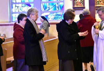 Bishop Schlert distributes Communion to sisters.