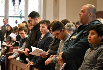 Catechumens join together in prayer during the Rite of Election.