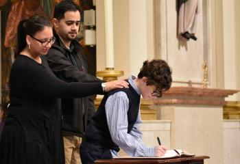Nolbert Gomez signs the Book of Elect, signifying his commitment and discipleship, with his sponsors, Yariel Delgado and Kristin Delgado, parishioners of Holy Infancy, Bethlehem.