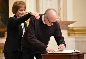 Jeff Gerstenblith, enrolls his name in the Book of Elect with the support of his sponsor, Joan McGorvey, parishioner of Our Lady of Mercy, Easton.