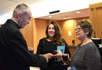 Monsignor Smith, left, talks with Paola Mattera, center, and Patty Huck.
