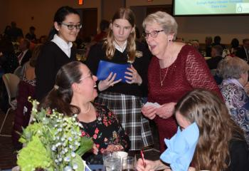 Sister Janice Marie Johnson, standing right, chats with a guest while helping student volunteers sell raffle tickets. From left are Sara Miller, LuLu Blewitt, Isabella Allen and Morgan Medvedz.